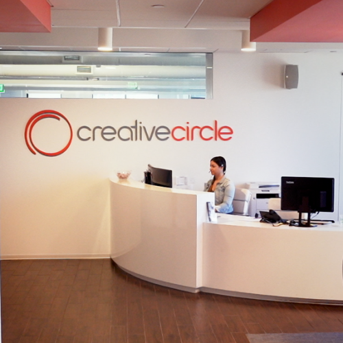 receptionist sits at desk at Creative Circle office