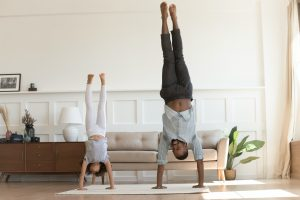 young girl and father doing handstands in living room