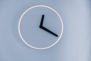 minimalist analog clock on blue-grey wall