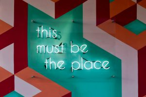 """neon sign that reads """"this must be the place"""" on vibrant background"""