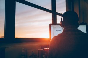 man sits in front of computer with sunset in background