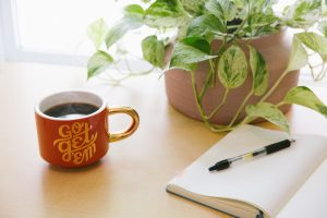notebook on wooden desk with cup of coffee and houseplant